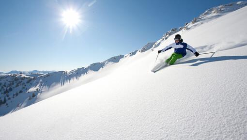 Skifahrer im Pulverschnee im Skigebiet Großarl im Salzburger Land. Perfekter Winterurlaub im Wellnesshotel direkt an der Piste.