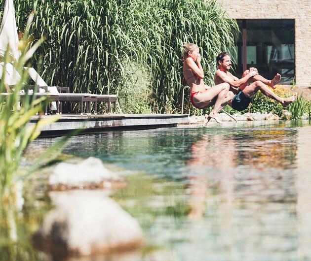 Paar springt in den Naturbadeteich der großen Badelandschaft vom Wellnesshotel Nesslerhof im Salzburger Land