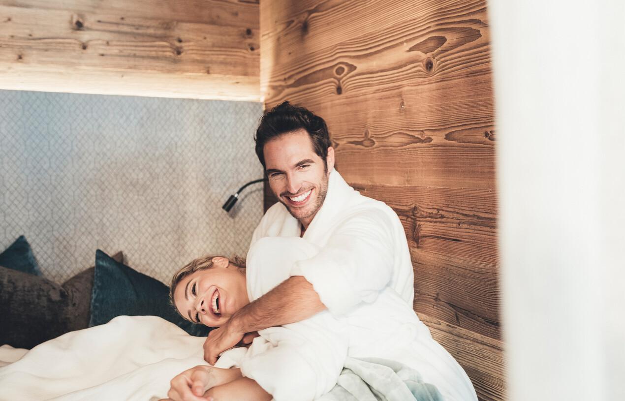 Lachendes Paar im Hotelzimmer beim romantischen Wellnessurlaub im Salzburger Land