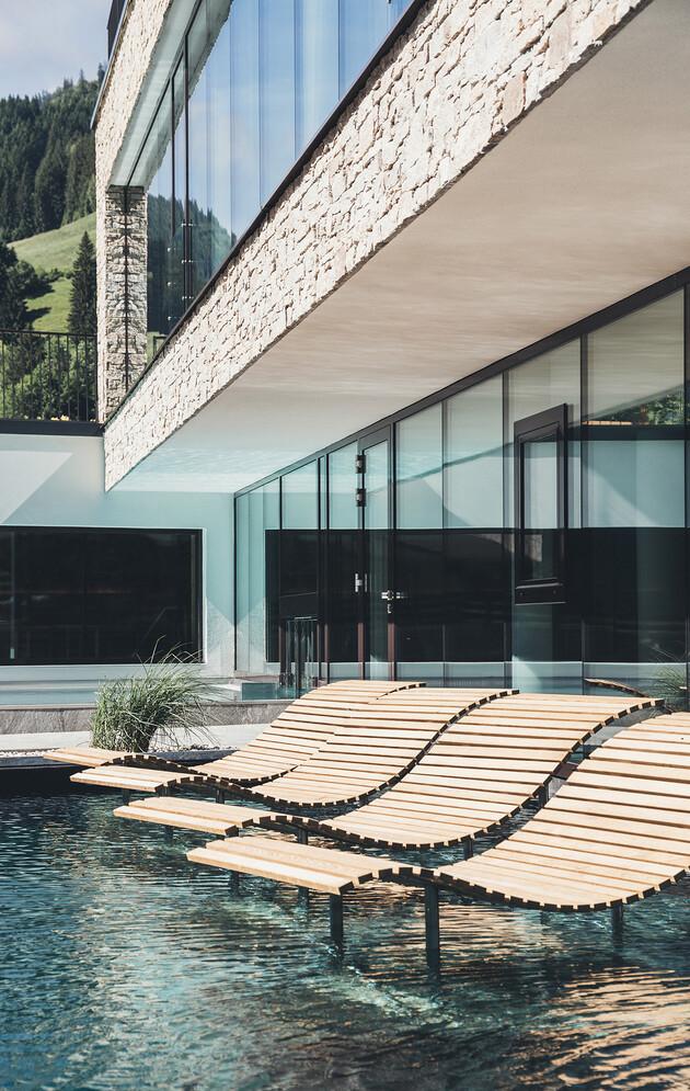 Sonnenliegen im Außenpool der großen Badelandschaft vom Wellnesshotel Nesslerhof im Salzburger Land