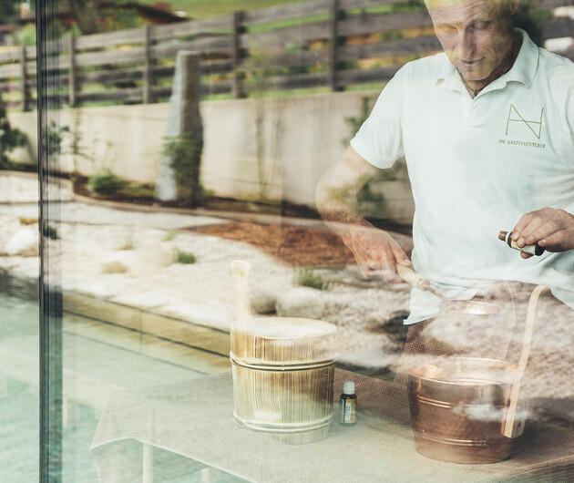 Der Saunameister beim vorbereiten des Aufgusses in der großen Saunalandschaft im Wellnesshotel Nesslerhof im Salzburger Land