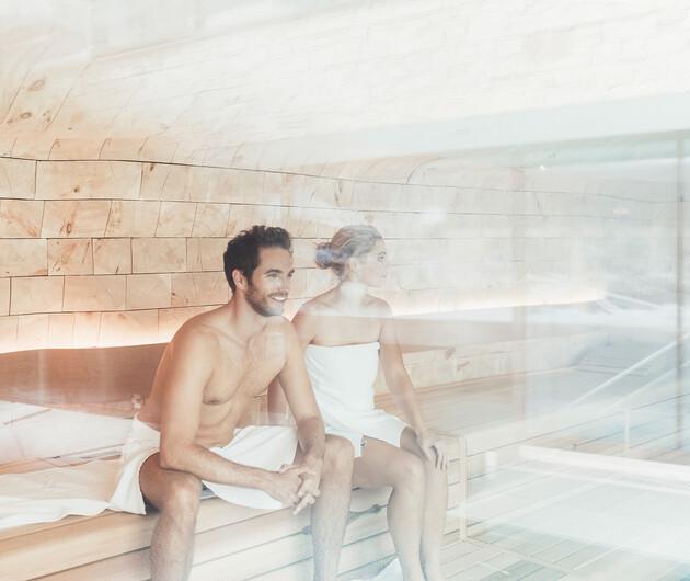 Paar in der Panorama-Sauna beim Winterurlaub im Wellnesshotel Nesslerhof in Salzburg