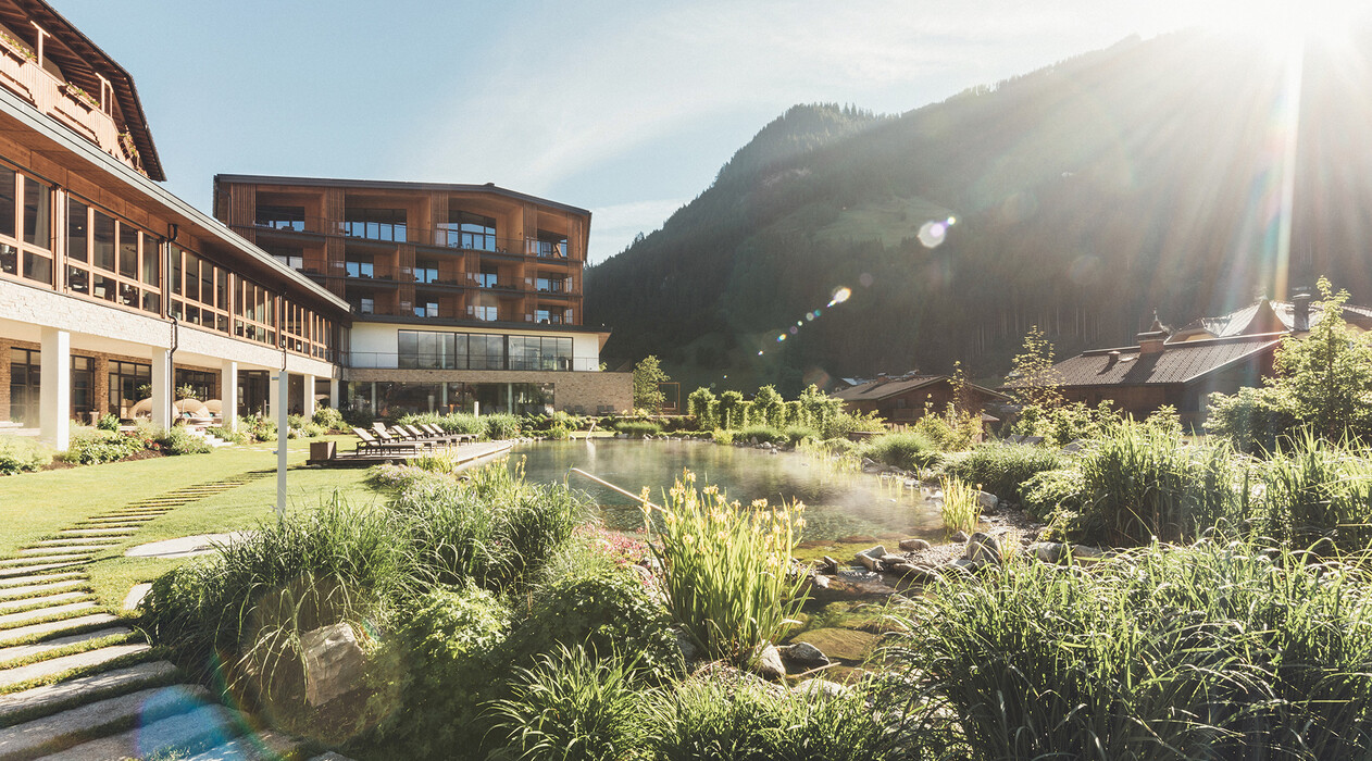 Außenansicht vom Naturbadeteich vor dem Hotel Nesslerhof mit der umliegenden Bergwelt vom Salzburger Land im Hintergrund