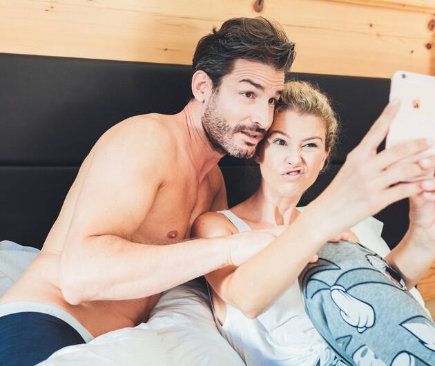 Paar beim Selfie machen im gemütlichen Doppelzimmer des 4*S Hotel Nesslerhof in Großarl
